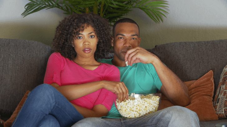 couple-watching-movie-on-couch-while-eat