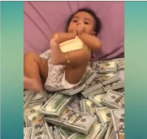 Nigerian Man Drops Bundles Of 100 Dollar Bills For His Child To Play With